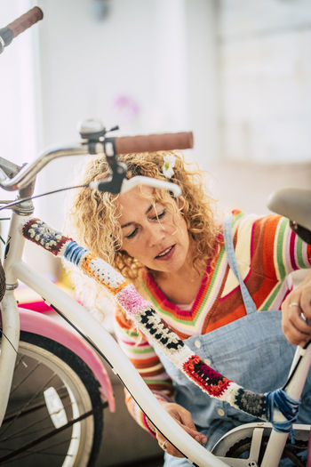 Mature woman sitting by bicycle outdoors