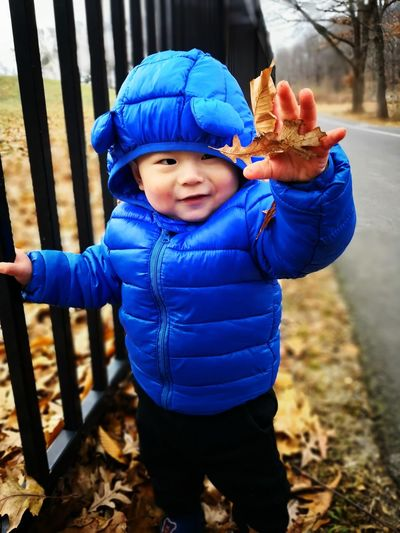 Cute baby boy wearing winter jacket while standing by railing