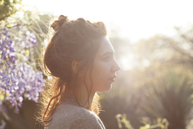 Side View Of Young Woman In Park On Sunny Day