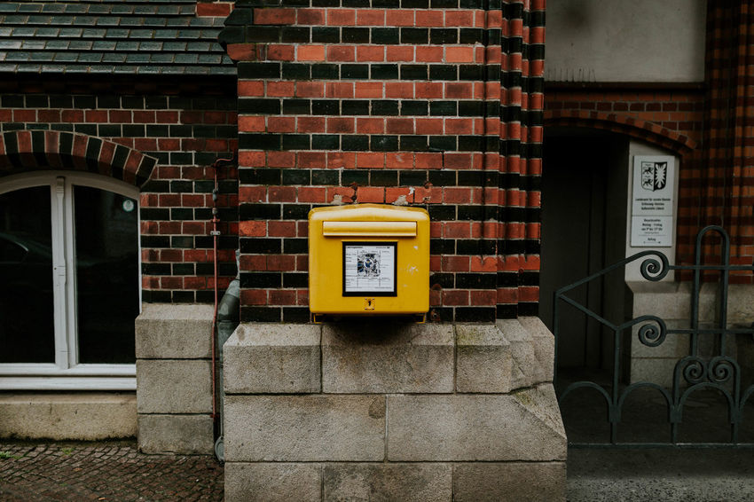 Brick Wall City Post Architecture Brick Brick Wall Building Exterior Built Structure City Close-up Communication Connection Day No People Outdoors Pay Phone Post Box  Public Mailbox Technology Telephone Booth Yellow Yellow Color