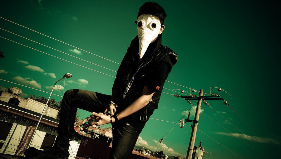 Man wearing mask while holding musical instrument against sky