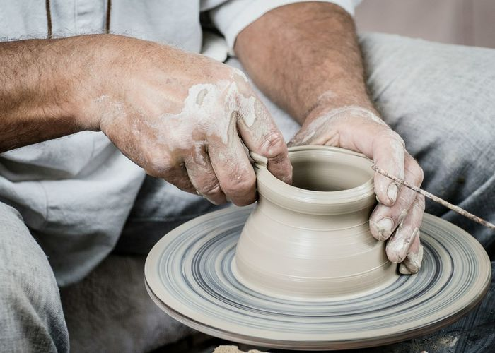 Midsection Of Man Making Clay Pots