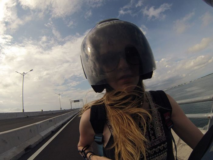 Woman wearing helmet while riding motorcycle on against sky