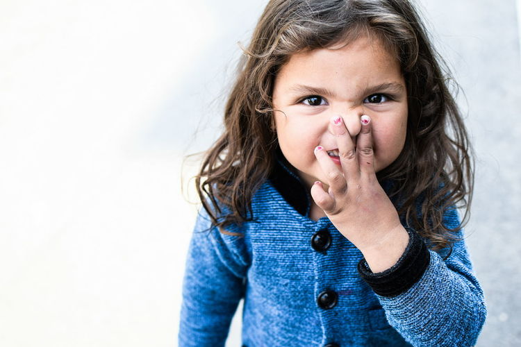 Portrait of girl holding nose