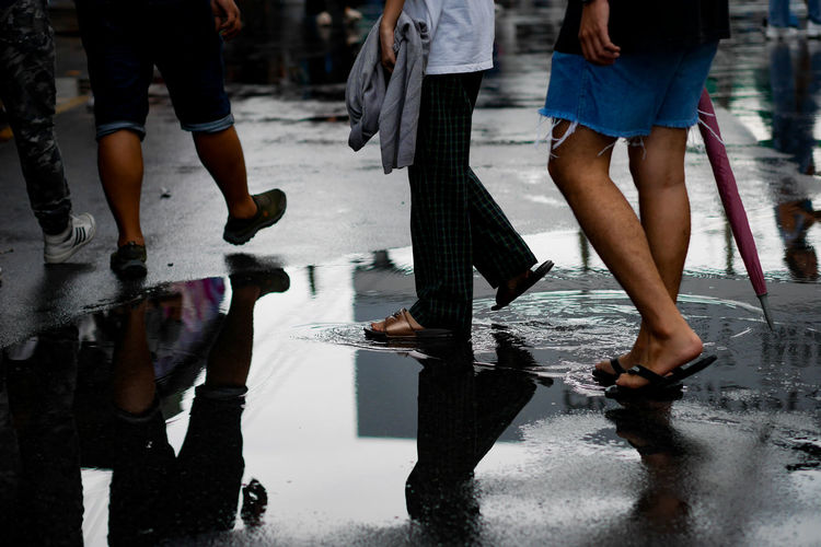 Low section of people walking on wet road