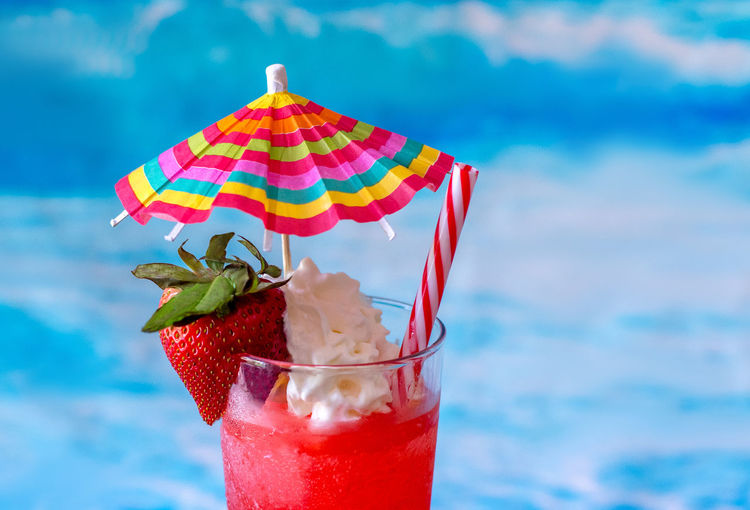 frosty frozen strawberry daiquiri cocktail with a colorful umbrella and whipped cream