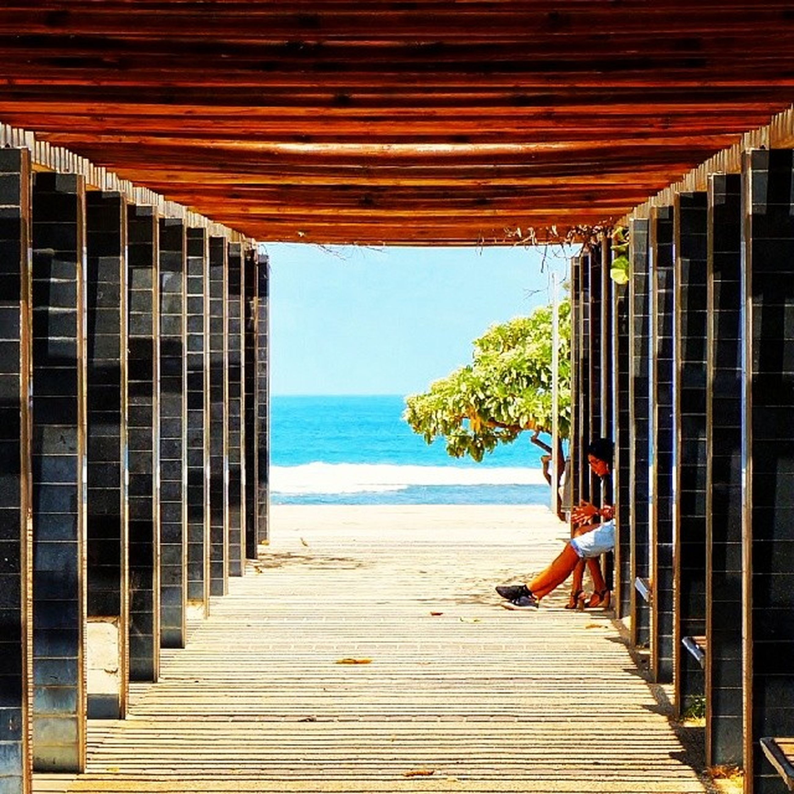 sea, built structure, horizon over water, architecture, the way forward, water, railing, sky, building exterior, beach, wood - material, tranquility, narrow, boardwalk, tranquil scene, blue, pier, scenics, day, nature