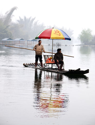Been There. Gui Lin China River Taxi Adult Day Full Length Lake Leisure Activity Lifestyles Men Nature Nautical Vessel Occupation Outdoors People Real People Reflection Sitting Sky Standing Togetherness Tree Two People Water Women