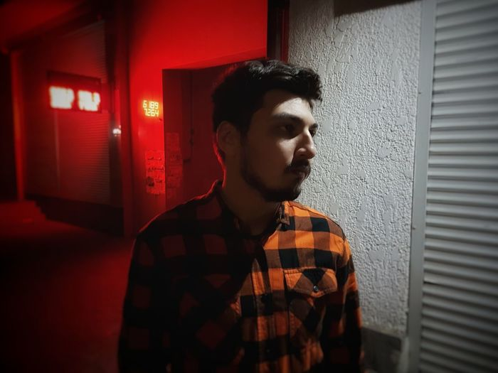 Portrait of young man standing against red wall