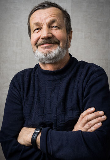 Smiling Senior Man With Arms Crossed Standing Against Wall