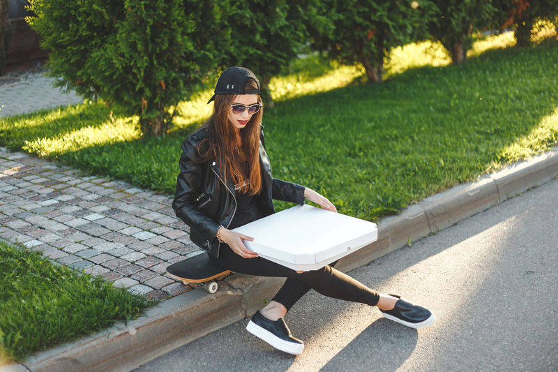 Young woman with pizza box sitting on skateboard against plants