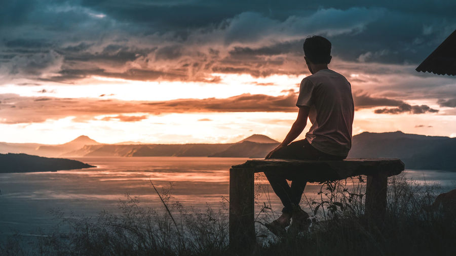 look at dusk. Sunset Sky Beauty In Nature Real People Cloud - Sky Scenics - Nature One Person Men Lifestyles Leisure Activity Rear View Sitting Tranquility Water Orange Color Tranquil Scene Nature Land Outdoors Looking At View Dusk INDONESIA Asian  Mountain Range