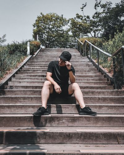 Full length of man sitting on staircase