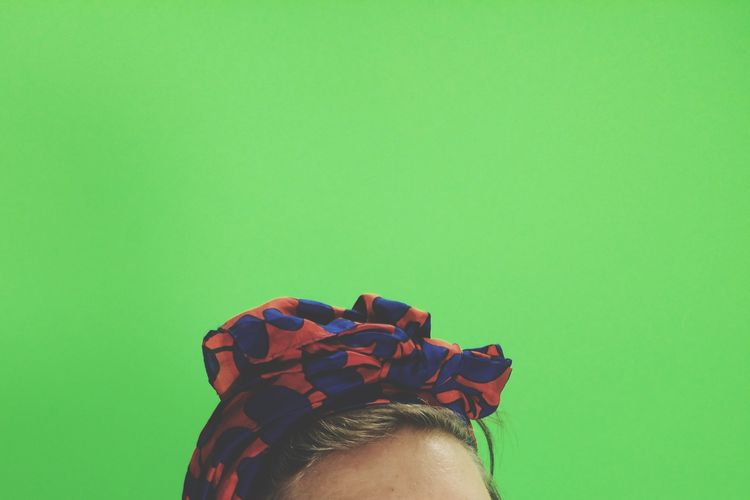 Cropped Image Of Woman Wearing Headscarf Against Green Background