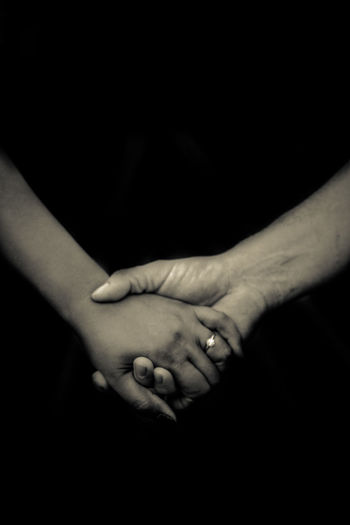 Close-up of couple hands against black background