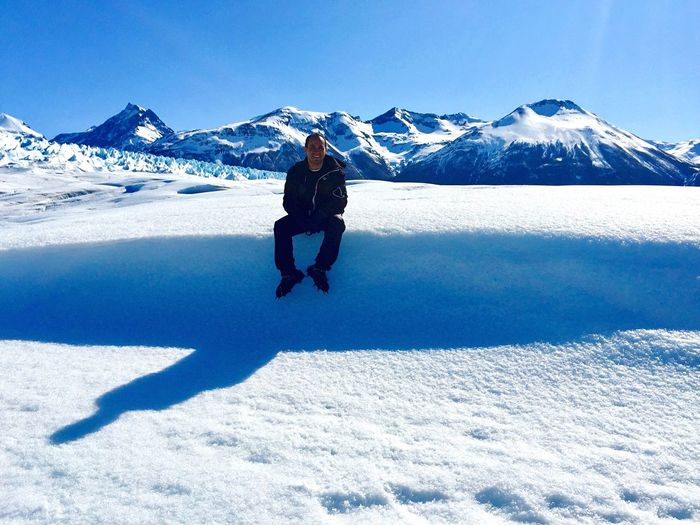 Man sitting on snowy field at glaciar perito moreno