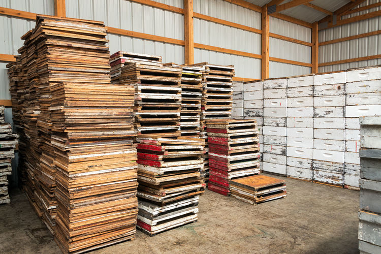 Stack of wooden pallets by beehives in storage room