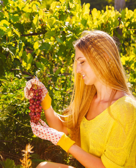 Midsection of woman holding strawberry outdoors