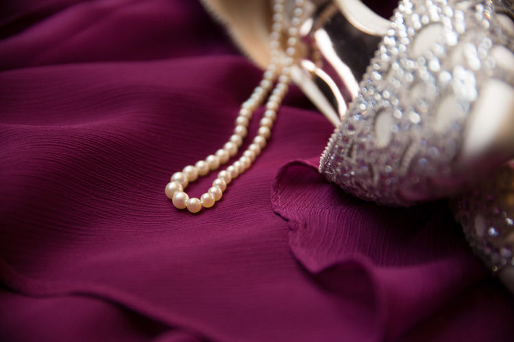 Close-up of pearl necklace and high heels on textile