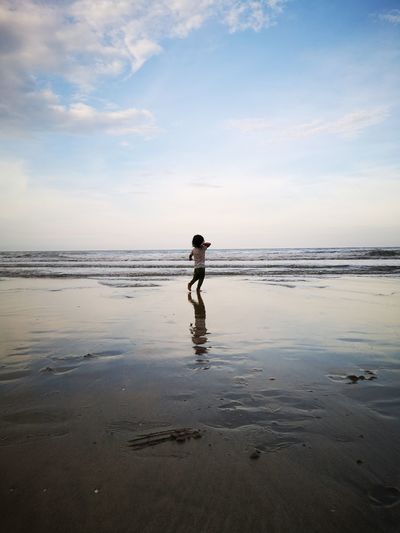 Baby girl playing at beach against sky