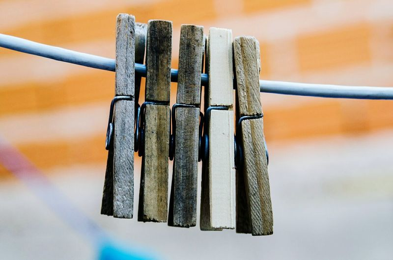 Close-up of wooden pegs hanging on clothesline