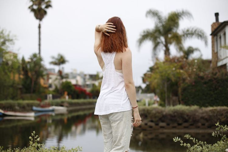 Rear view of woman standing against plants