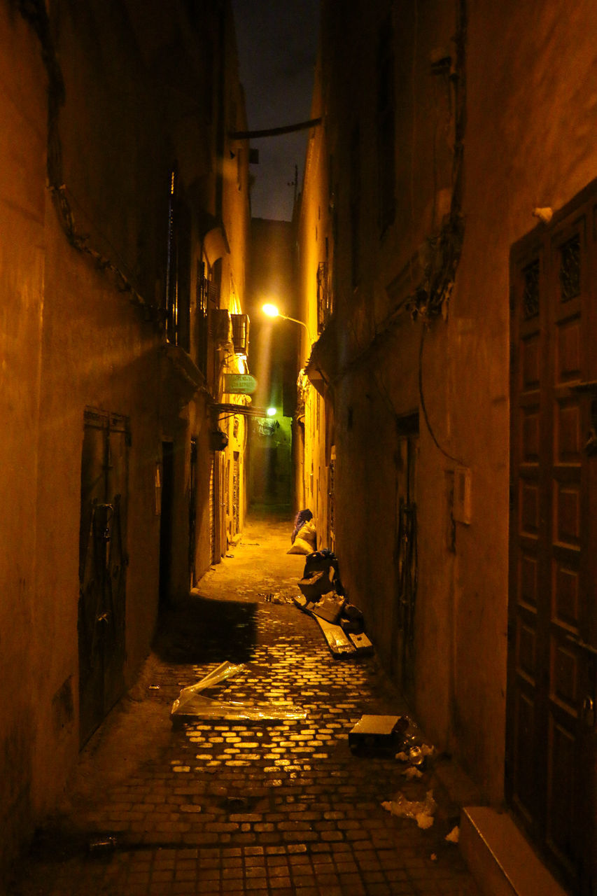 STREET AMIDST BUILDINGS AT NIGHT
