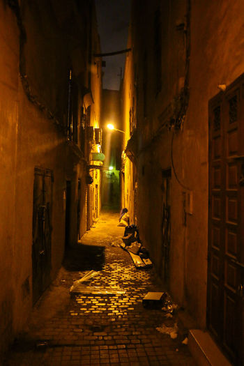 Narrow street amidst buildings in city at night