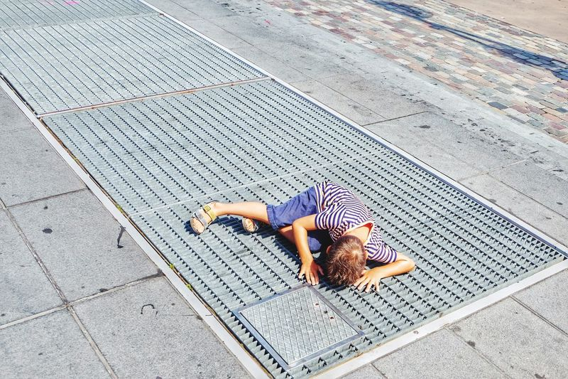 High Angle View Of Boy Looking In Gutter Through Metal Grate On Footpath