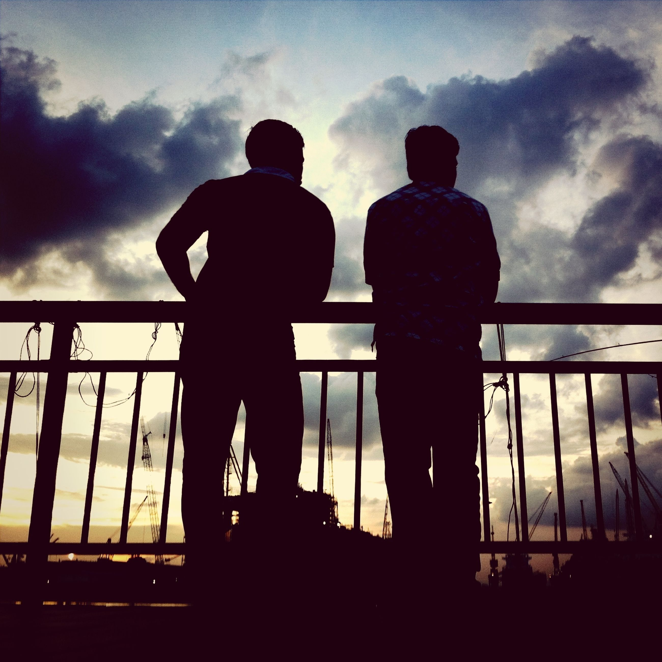 silhouette, sky, cloud - sky, men, standing, cloudy, low angle view, cloud, rear view, lifestyles, railing, leisure activity, person, built structure, outdoors, togetherness, architecture