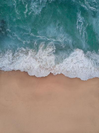 High angle view of waves rushing at beach