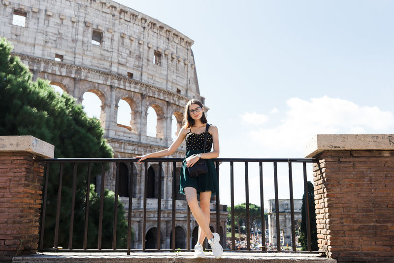 Woman by historic building against sky