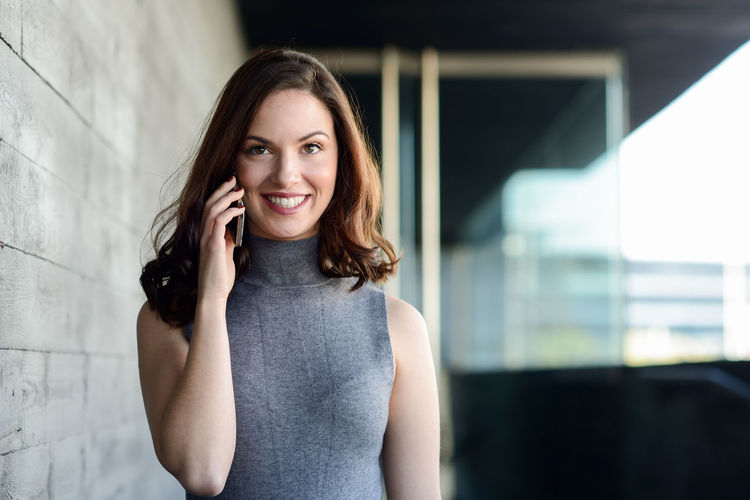 Smiling Young Woman Talking On Mobile Phone By Wall