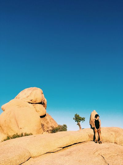 Rear view of man standing on desert against clear blue sky