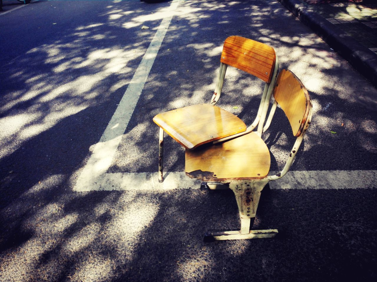no people, sunlight, shadow, day, high angle view, nature, street, wood - material, city, road, seat, outdoors, still life, absence, close-up, transportation, footpath, empty, sidewalk, table