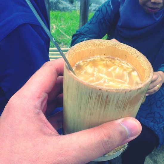 Ginger spice tea with a dash of milk and shredded coconut served hot in a bamboo cup Nongkrong Di Bandung