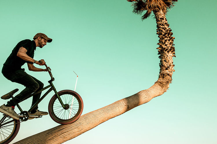 Low angle view of man with bicycle against clear sky