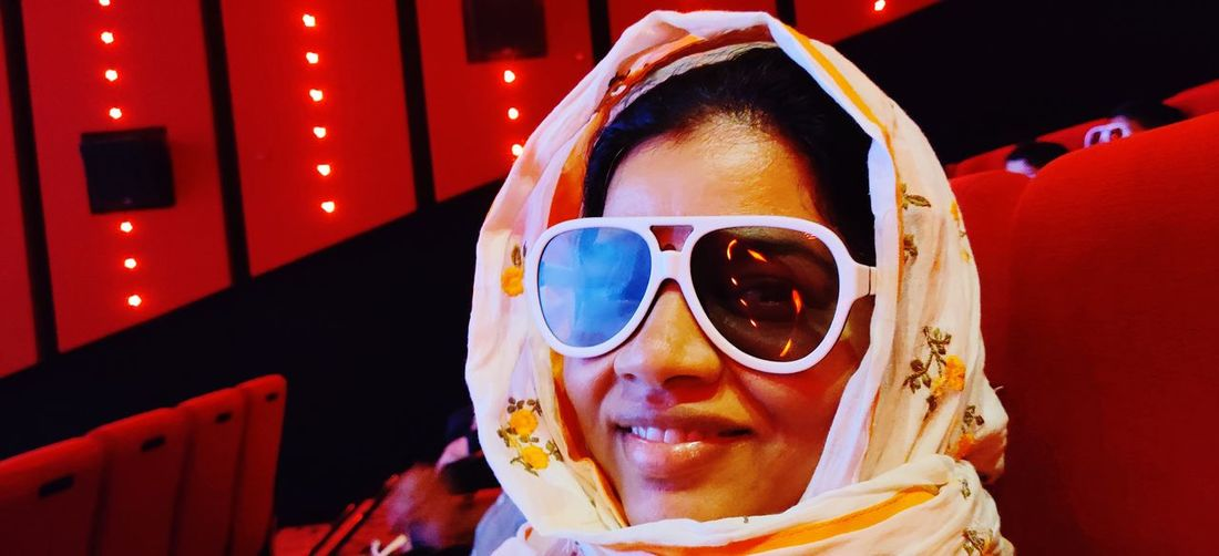 Close-up portrait of woman wearing 3-d glasses in movie theater