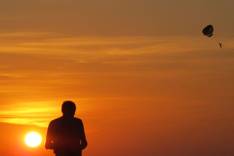 Rear view of silhouette man standing against orange sky at sunset