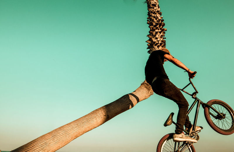 Low angle view of man cycling on bicycle against clear sky