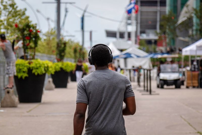 Rear View Of Young Man Listening Music While Walking On City Street