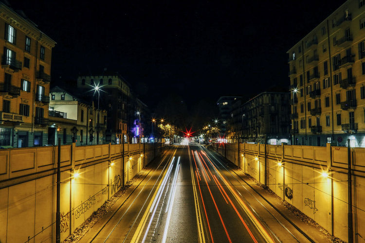 Light trails on city street amidst buildings at night