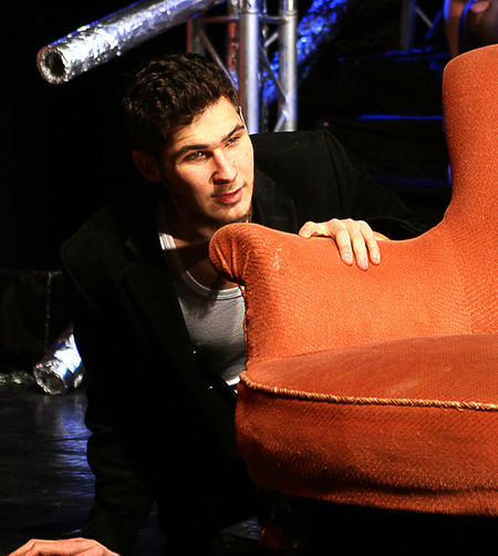 Young man by brown armchair on stage
