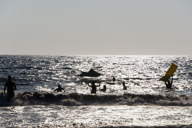 SILHOUETTE OF People playing, swimming in the waves in the island of Patmos, Greece in summer time Beauty In Nature Clear Sky Day Horizon Horizon Over Water Land Leisure Activity Lifestyles Men Motion Nature Outdoors People Real People Scenics - Nature Sea Silhouette Sky Water Wave