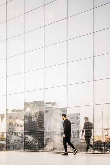 People walking on glass wall in city