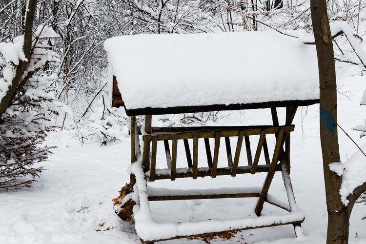Snow covered bench on field during winter