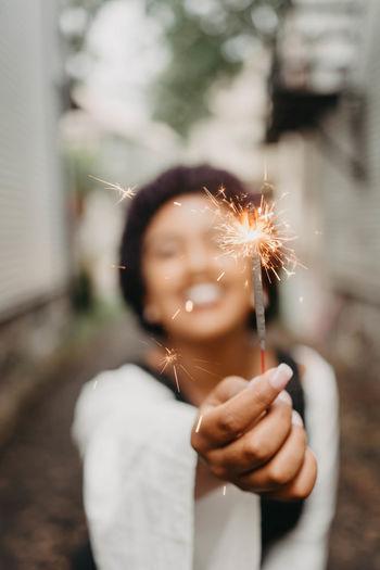 Smiling woman holding lit sparkler in city