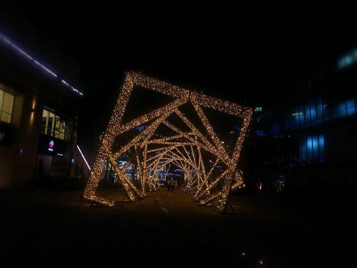 Illuminated christmas lights on street in city at night