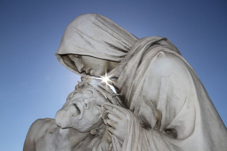 Statue Of Pieta Against Clear Blue Sky