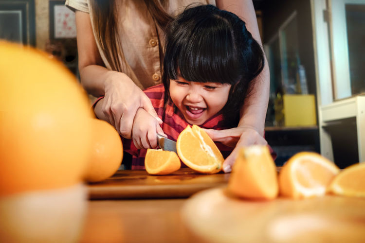 Happy Cute 3-4 Years Old Girl with her Mom Slice some Orange on Wooden Table in Pantry Room. Young Girl is Learning Cook with her Mother. Fruit and Vegetable for Kids Concept Orange Kids Girl SLICE Learning Mother Mom Happy Teach Class School Parent Smile Summer Playful Concept Face Smiling Children Fun Cook  Kitchen Pantry Lifestyle Portrait Joy Happiness Cheerful Childhood Model 3 Years Fruit Food Sliced Healthy Organic Juicy Citrus  Health Freshness Cut Knife Juice Wooden House Copy Space Innocence Headshot Emotion Preparing Food